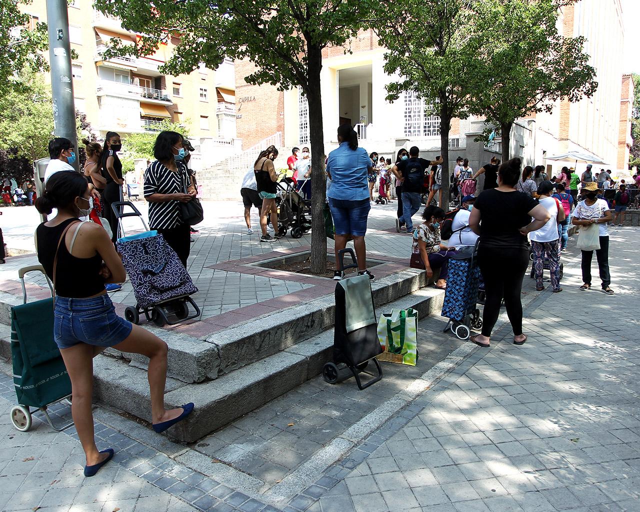 Colas del hambre. Decenas de personas esperan para recoger alimentos en una parroquia en el barrio de Tetuán. Madrid. 28/07/2020.