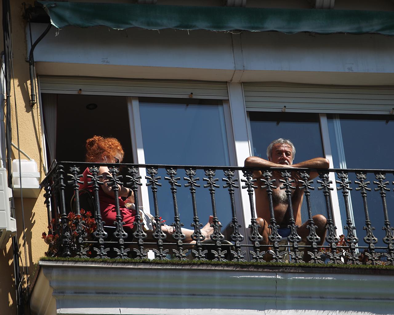 Dos personas toman el sol desde su terraza en Puente de Vallecas. Madrid. 26/03/2020.