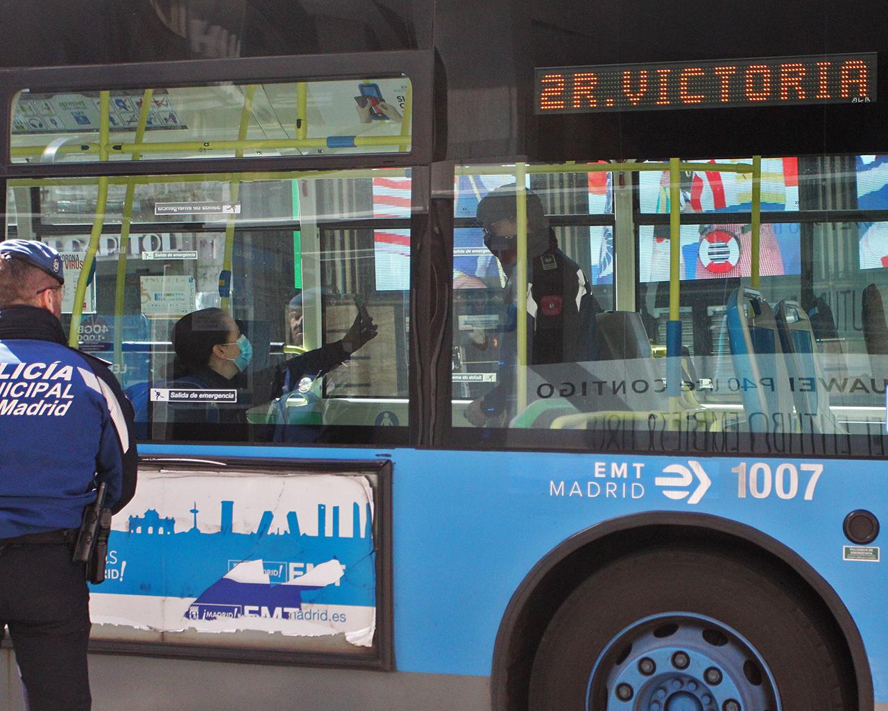 Una usuaria de transporte muestra documentación a la Policía Municipal en un control en Gran Vía. Madrid. 26/03/2020.