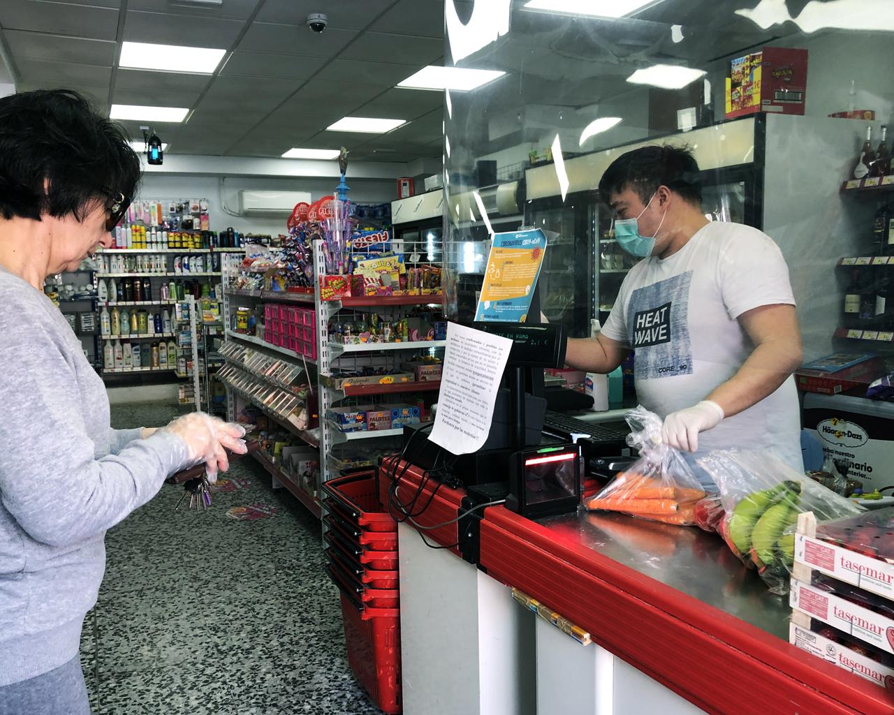 Un comerciante chino atiende a un cliente tras una mampara de plástico. Madrid. 14/03/2020.