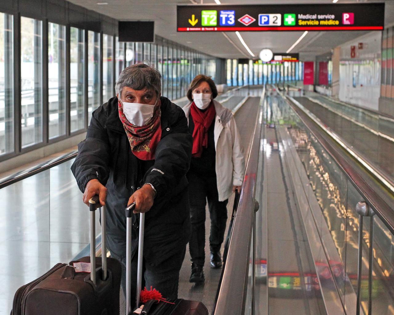 Dos turistas se marchan de Madrid en la Terminal 2 del Aeropuerto Adolfo Suárez Madrid Barajas. Madrid. 18/03/2020.