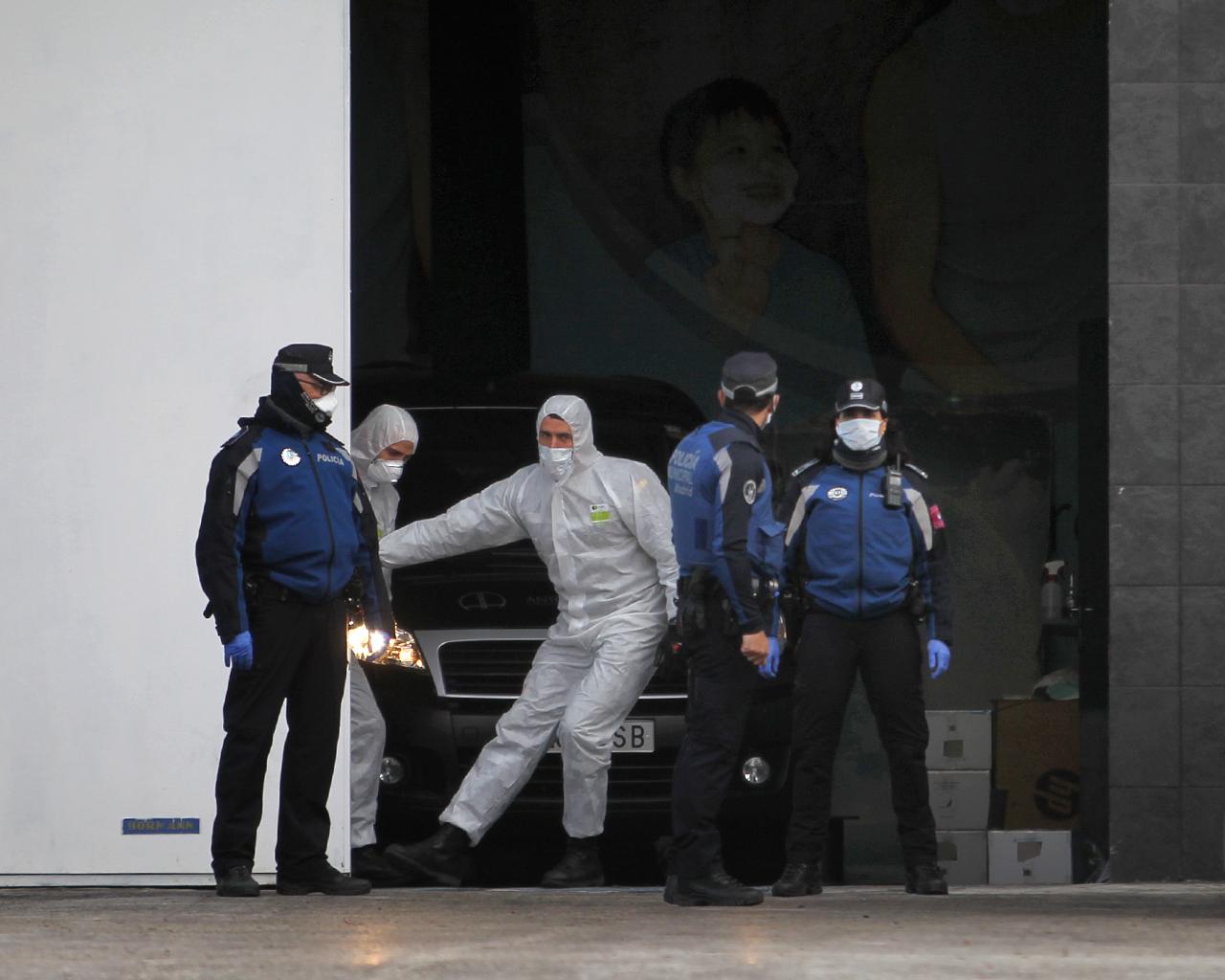 Un operario cierra la puerta de acceso a vehículos funerarios en el Palacio de Hielo. Madrid. 24/03/2020.