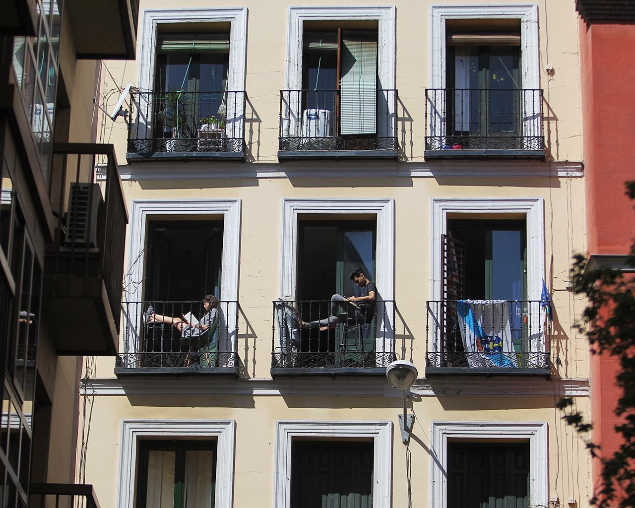 Dos jóvenes confinados leen en el balcón de casa. Madrid. 25/03/2020.