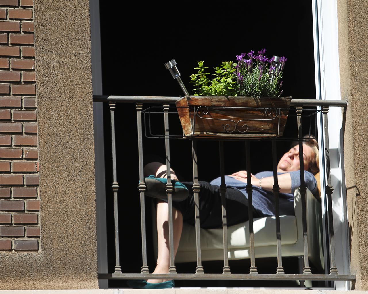 Una mujer toma el sol desde el balcón de su casa. Madrid. 25/03/2020.