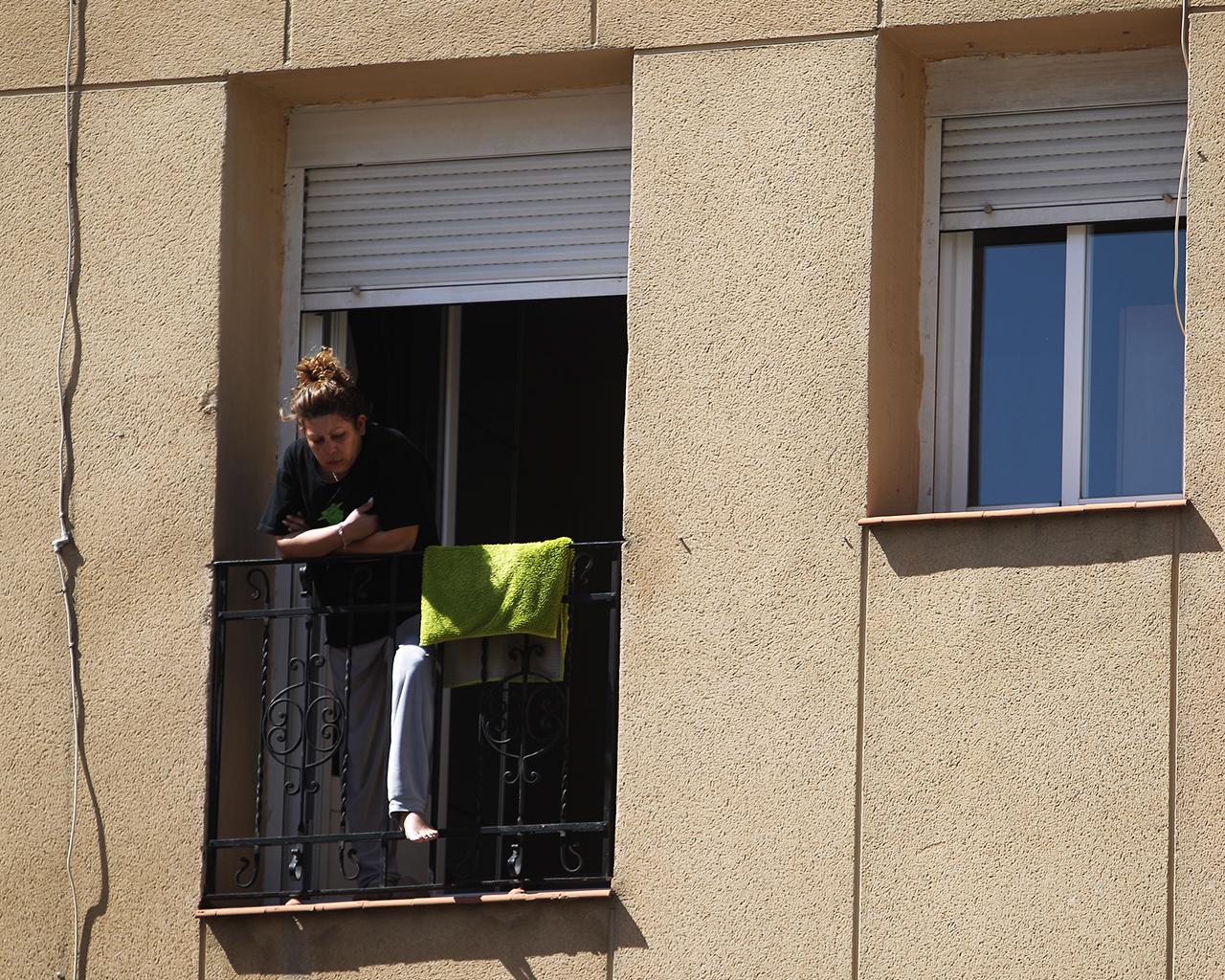 Una mujer observa desde su balcón, en Madrid. 26/03/2020.