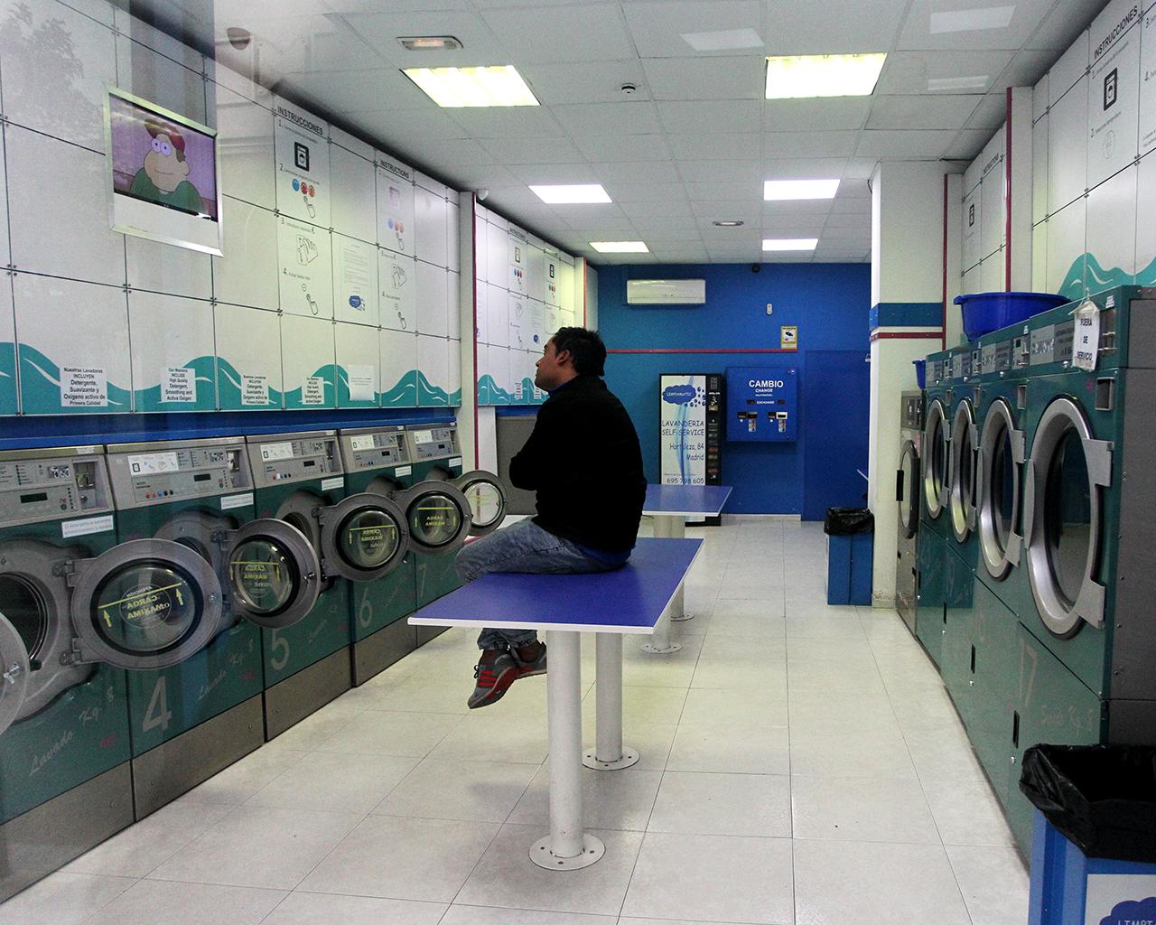 Un hombre espera el lavado de su ropa en una lavandería. Madrid. 30/03/2020.