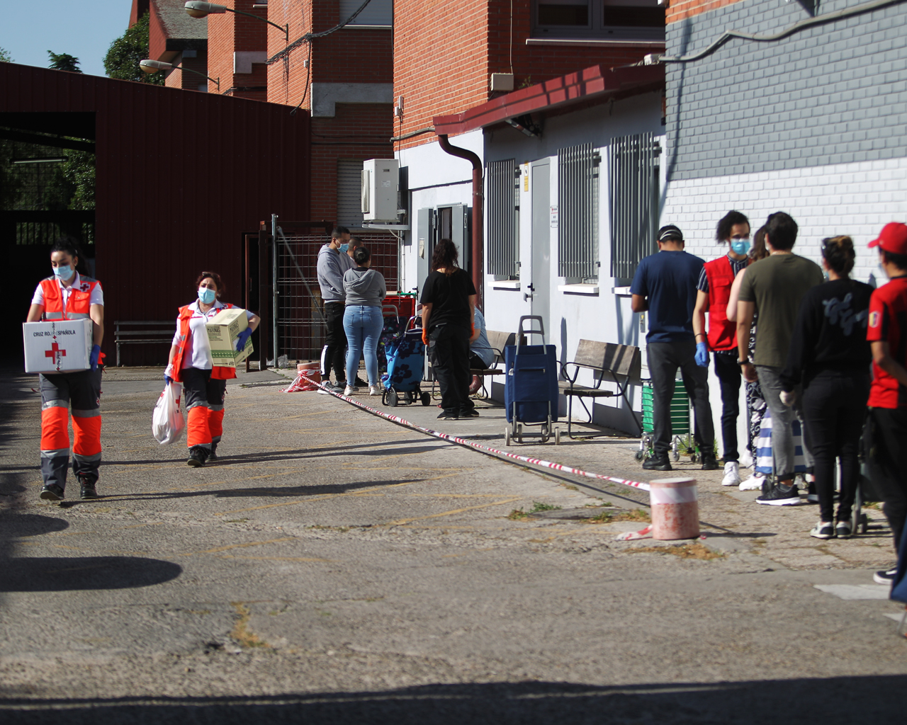 Decenas de personas esperan a ser atendidas para recoger alimentos de primera necesidad en Cruz Roja. Madrid. 08/05/2020.