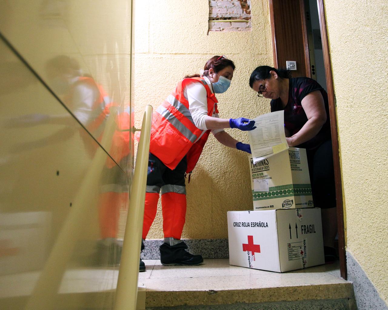 Dos voluntarias de Cruz Roja reparten comida a familias con necesidades en Getafe, Madrid. 08/05/2020.